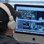 man sits at computer editing video
